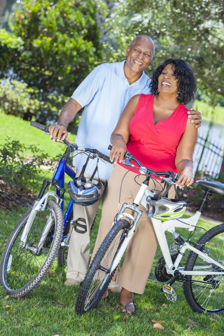 A senior African American woman & man couple riding bicycles in the summer